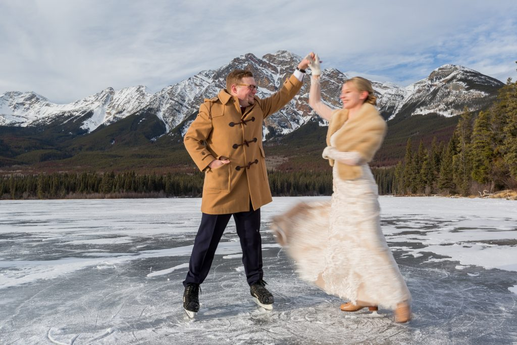 Photo of wedding couple wearing skating across Pyramid Lake during their winter wedding