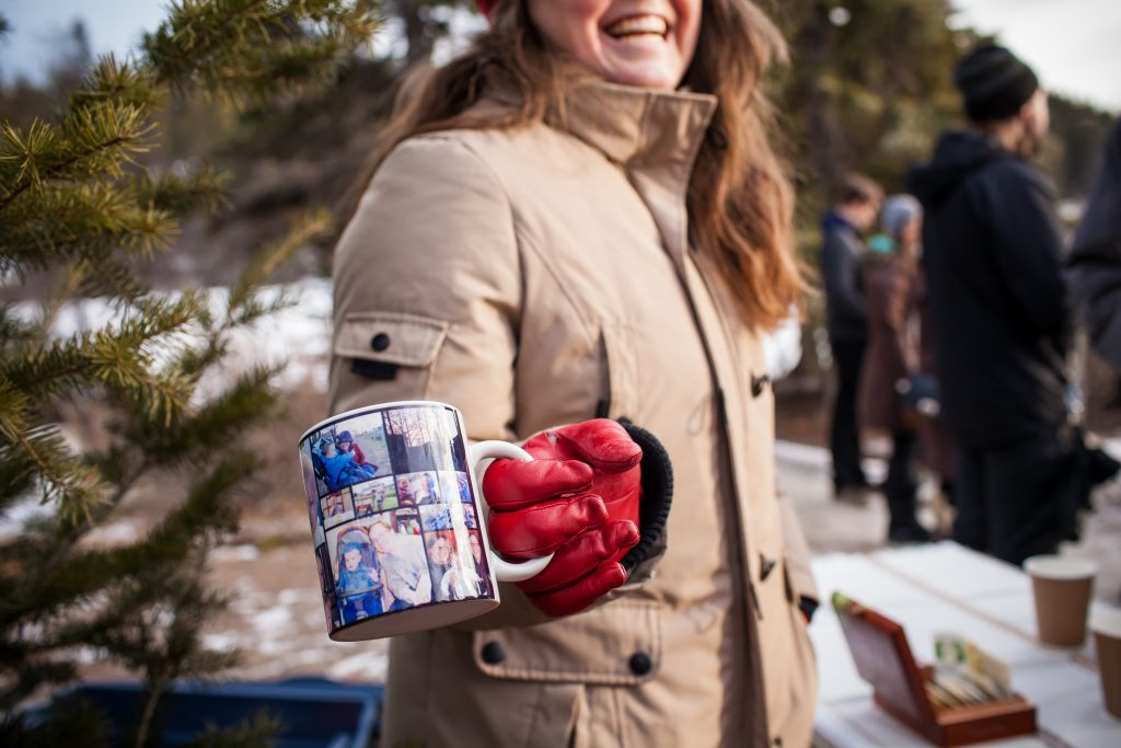 Eco Friendly wedding guests brought their own mugs for mulled wine during outdoor winter wedding ceremony at Pyramid Lake in Jasper