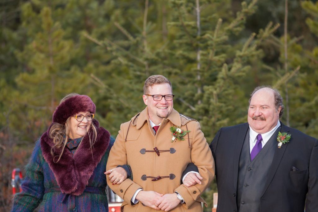 Groom and his parents walking in during wedding ceremony in Jasper at Pyramid Lake