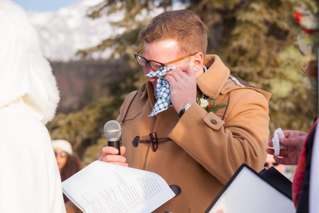 Photo of the groom getting emotional during his wedding vows at Pyramid Lake in Jasper