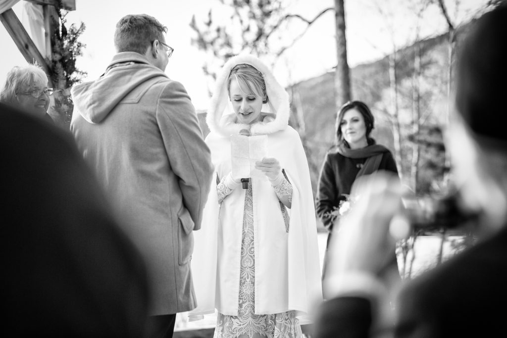 Bride reading her vows during intimate winter wedding ceremony in Jasper