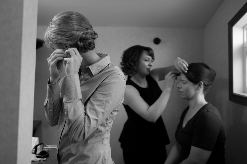 Bride putting on her earrings while getting ready for wedding ceremony at Pyramid Lake
