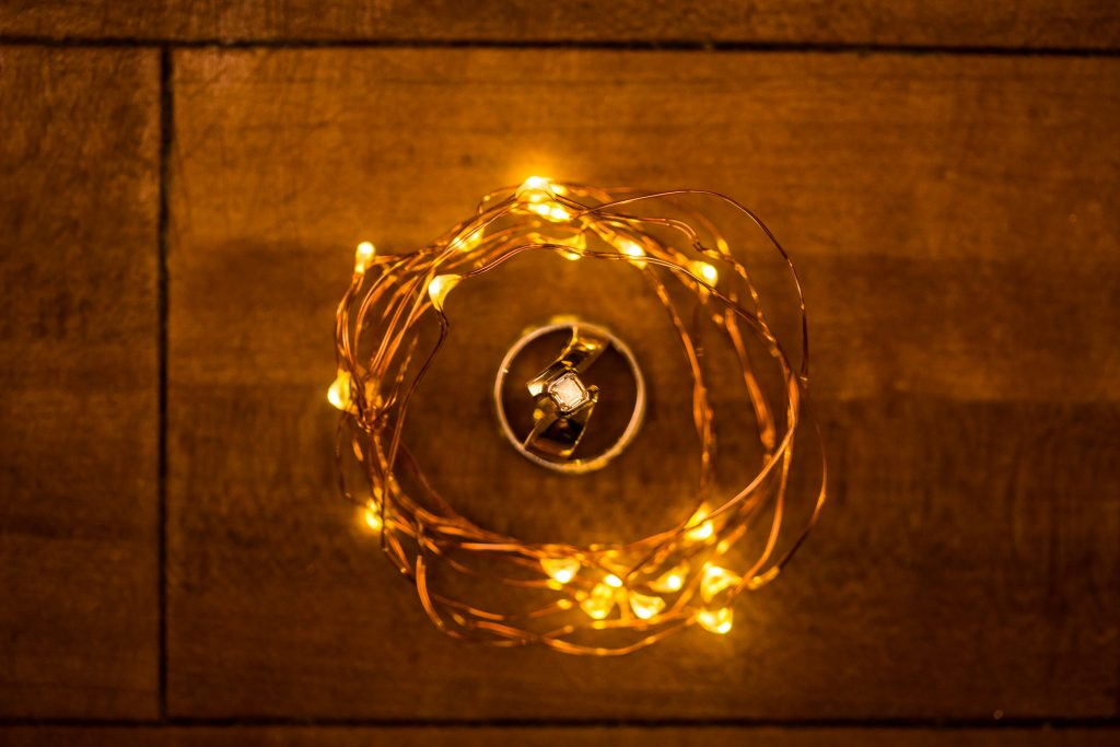Detail photo of wedding rings wrapped up in fairy lights
