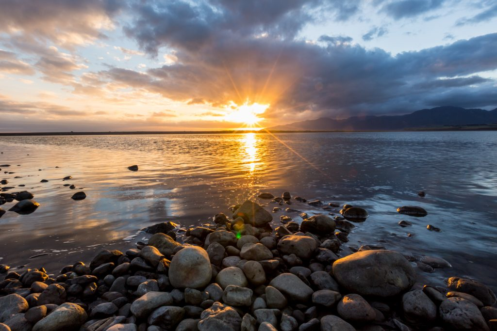 a picture of sunset at Lake Ferry over the rocks on the beach