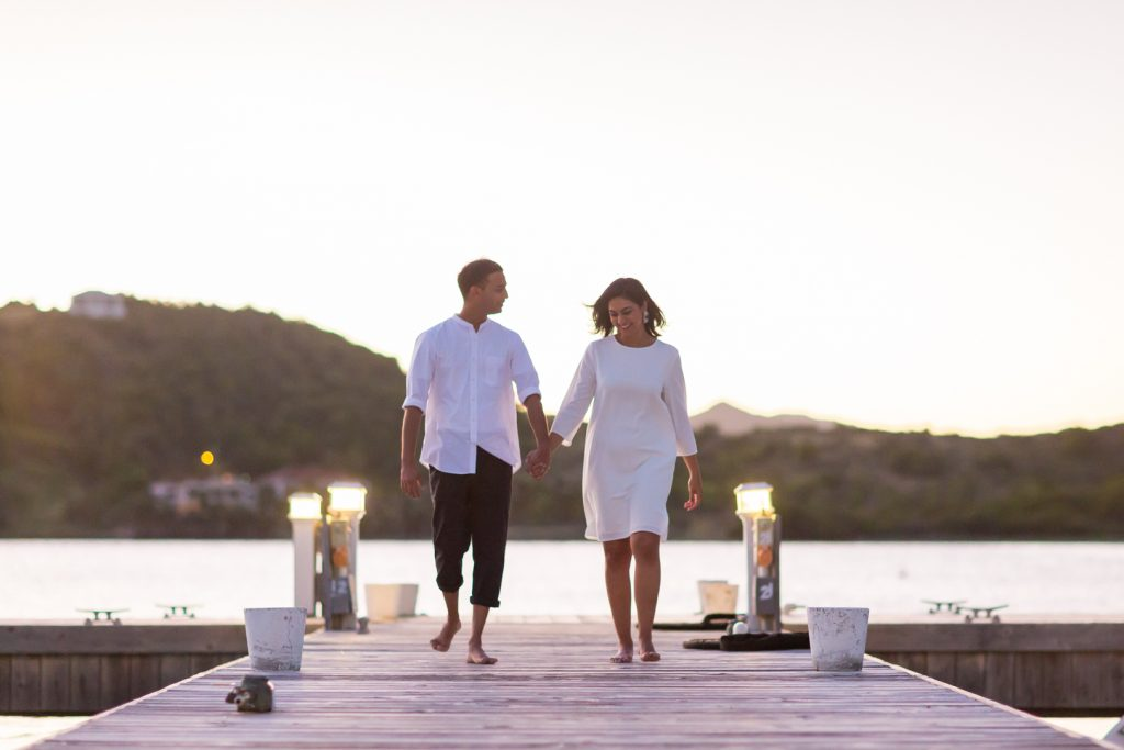 Antigua engagement picture of couple holding hands on the pier