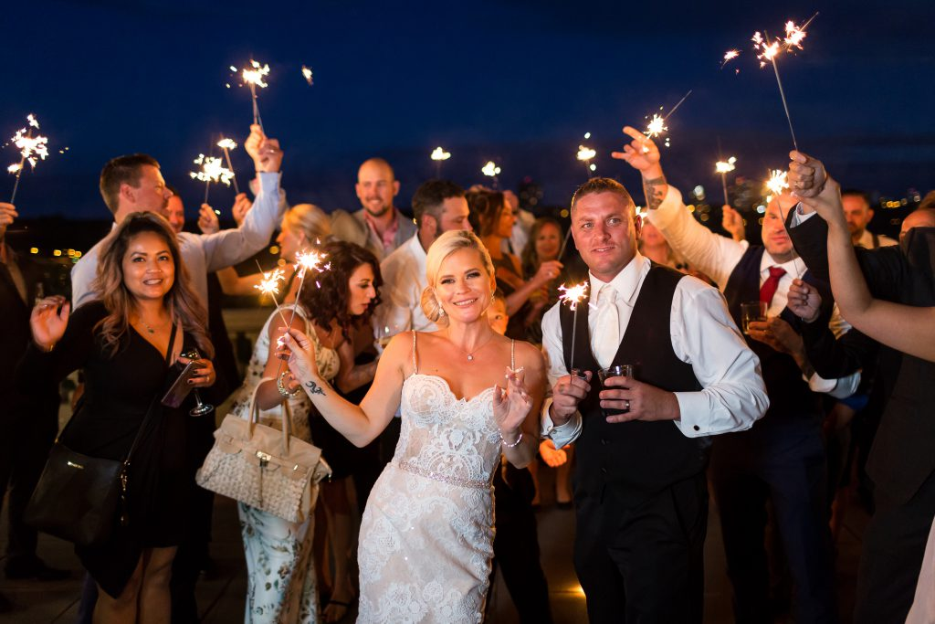 Sparkler photo with bride and groom with wedding guests