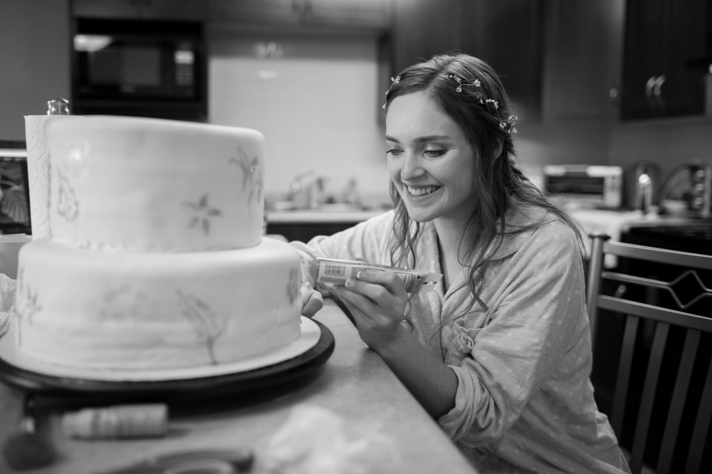 Bride decorating the wedding cake
