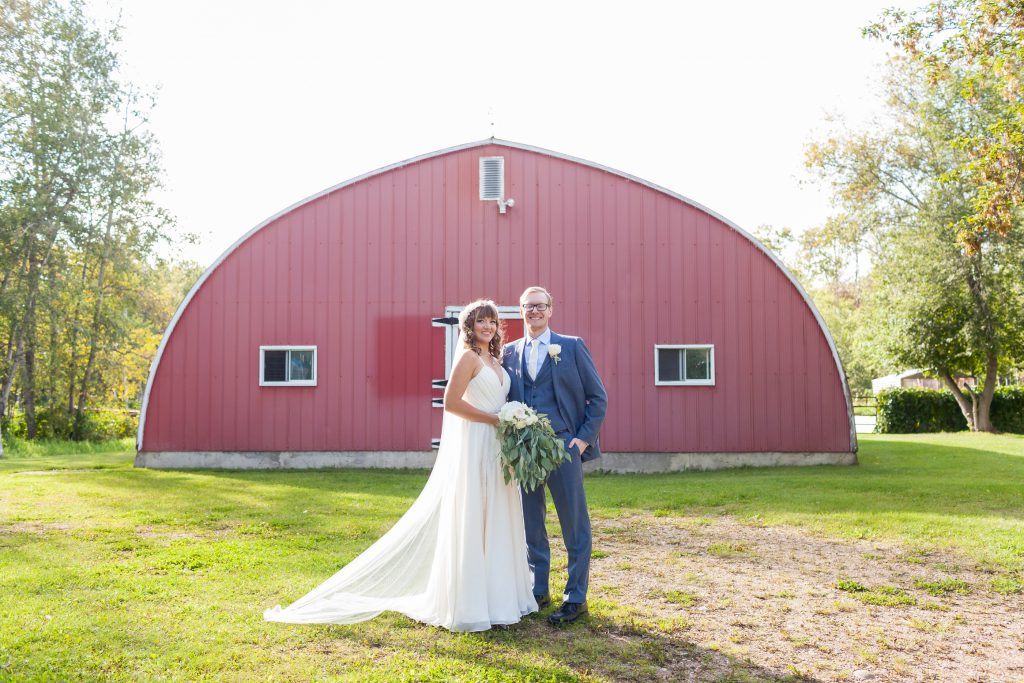 bride and groom portrait with red barn