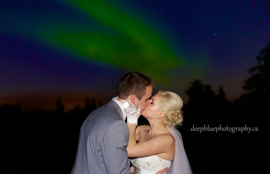 Bride and Groom Kiss Under Northern Lights