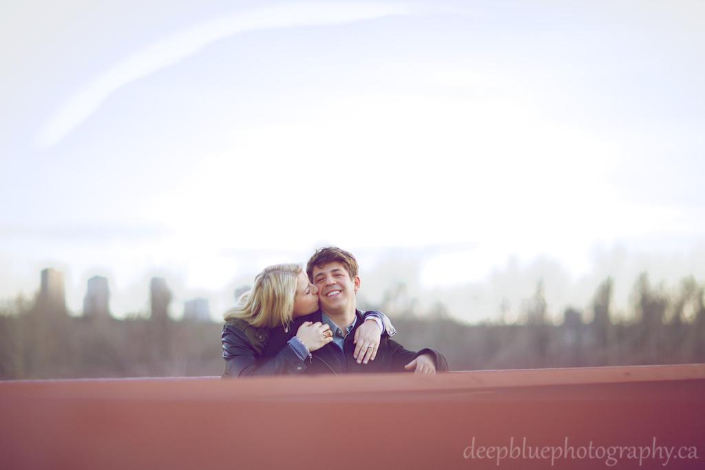 Photo of Megan Kissing John on the Bridge - Louise McKinney Park Engagement Photography