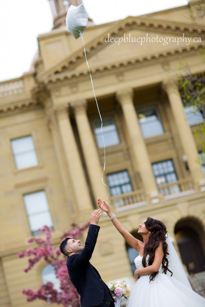 Photo of bride and groom releasing a balloon at the Legislature grounds