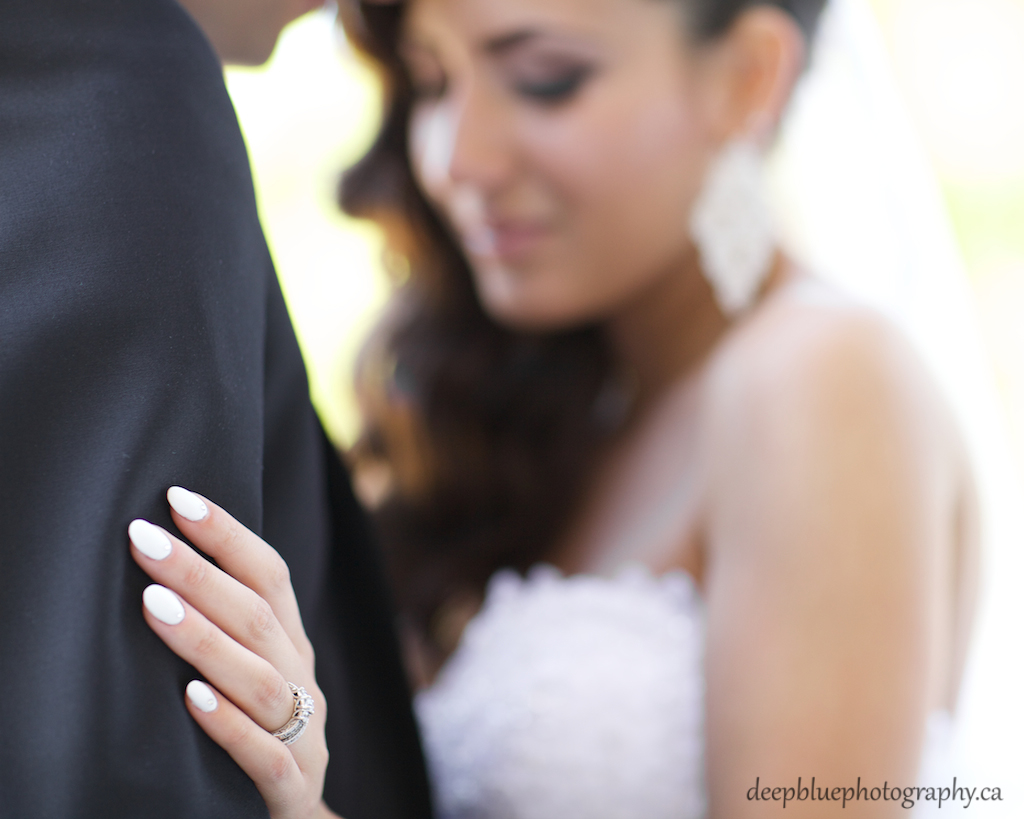 Photo of bride holding groom's arm, showing her wedding ring