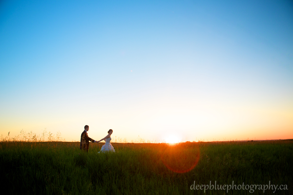 Bride leads groom through wheat field at sunset