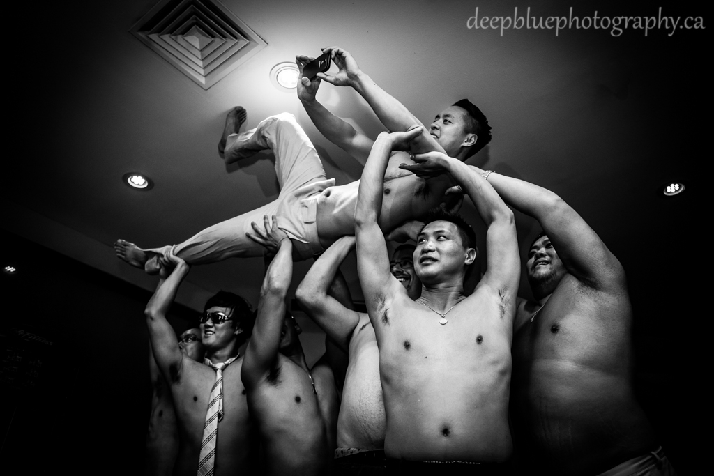 Photo of groomsmen lifting groom