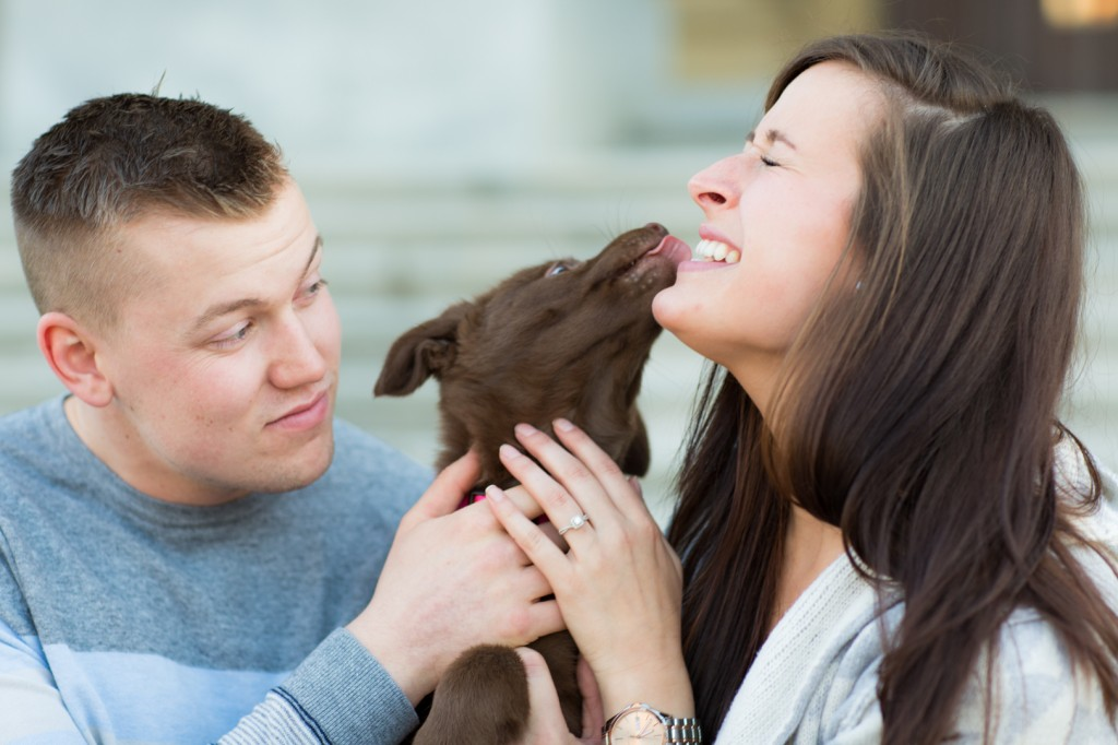 A picture of a couple getting engagement Pictures With their Dog