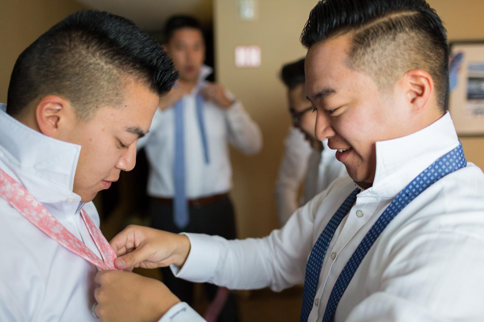 photo of groom putting on tie