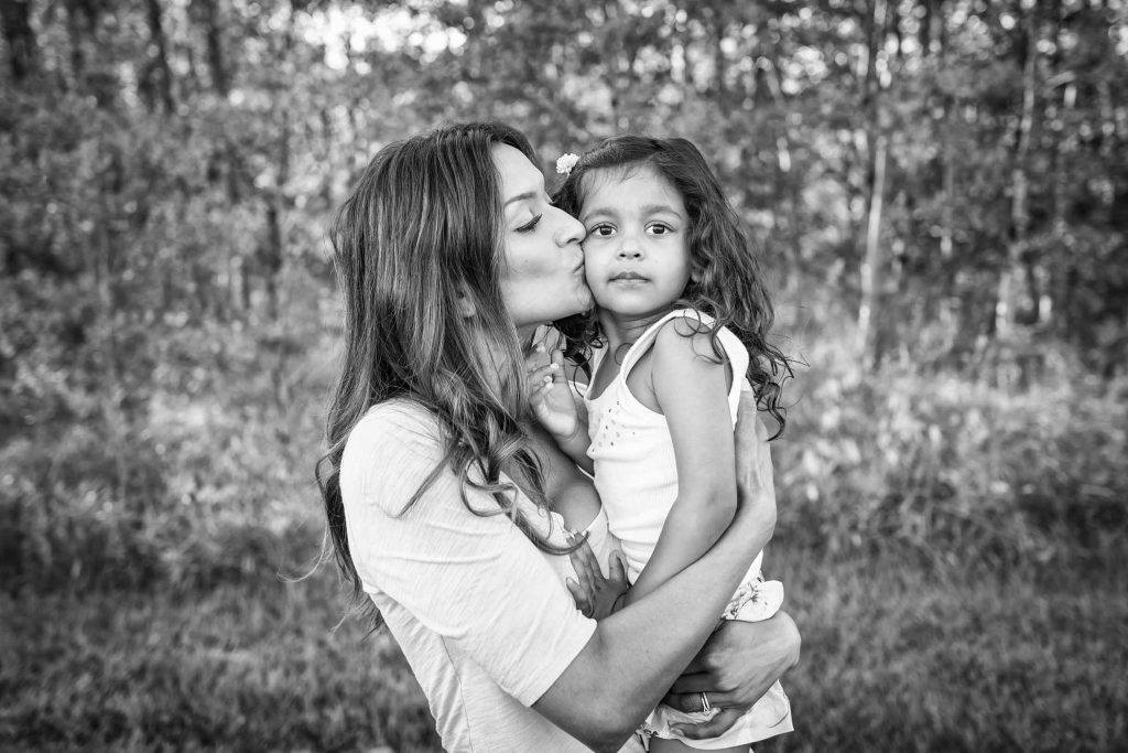 Mom kissing her daughter black and white