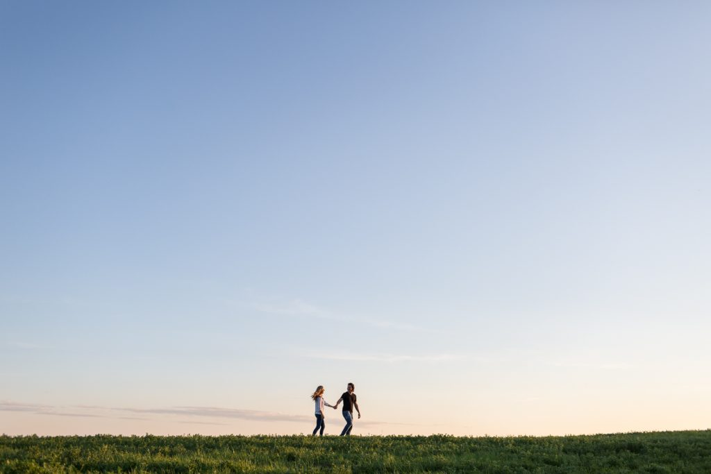 Couple walking through country pasture during engagement session