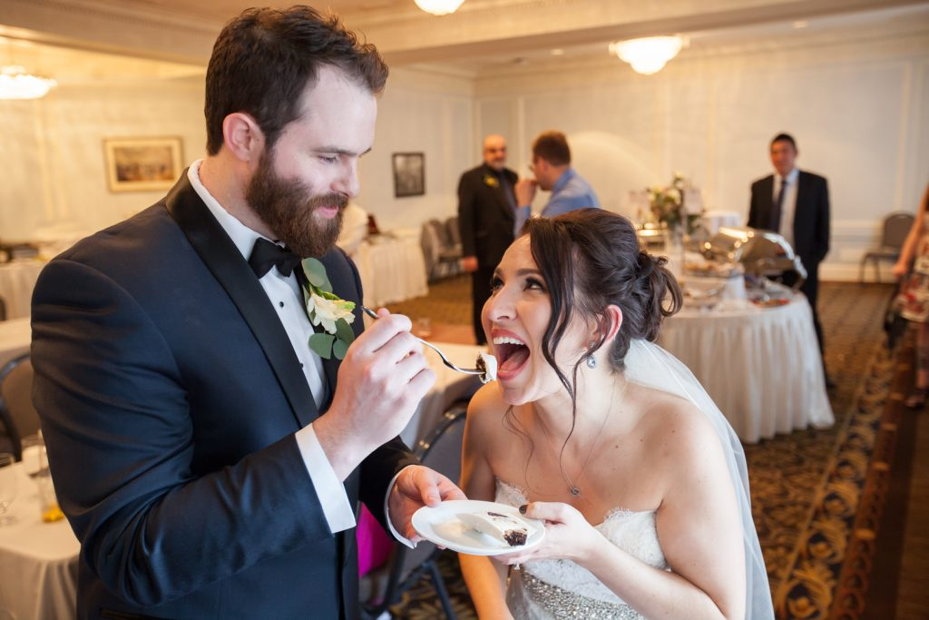 Groom feeding the bride a piece of wedding cake