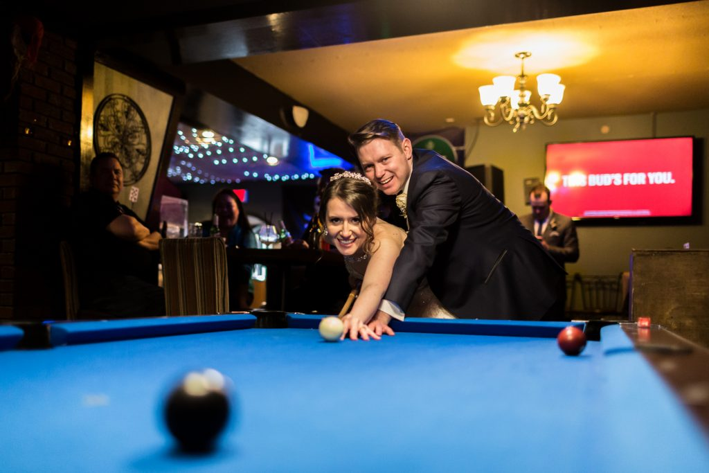 Bride and groom playing pool in the local bar