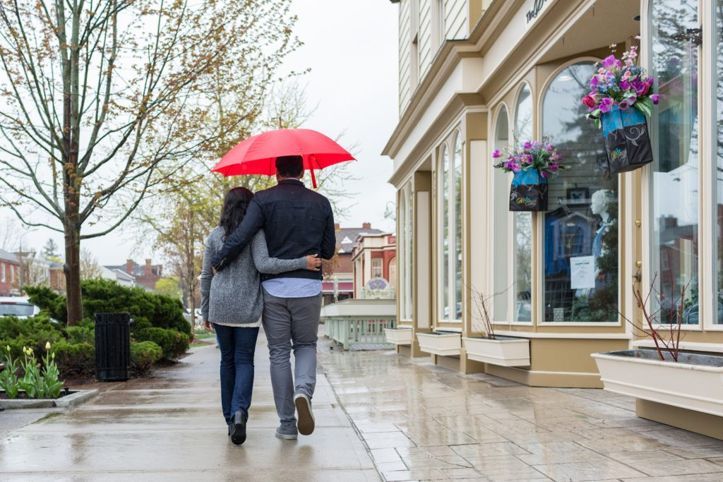 Couple with red umbrella walking down the street - Niagara on the Lake Engagement Photography