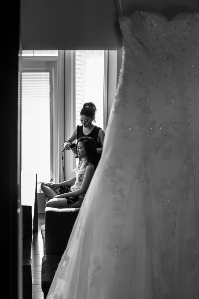 Bride sitting and getting her hair done with her wedding dress hanging in the foreground