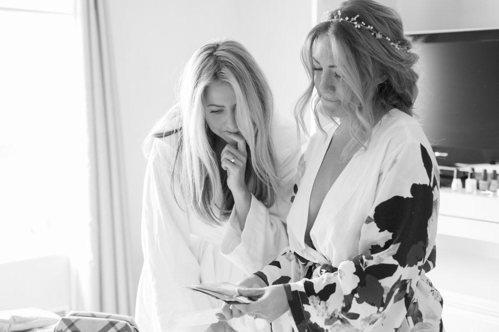 Bride and bridesmaid looking at photos