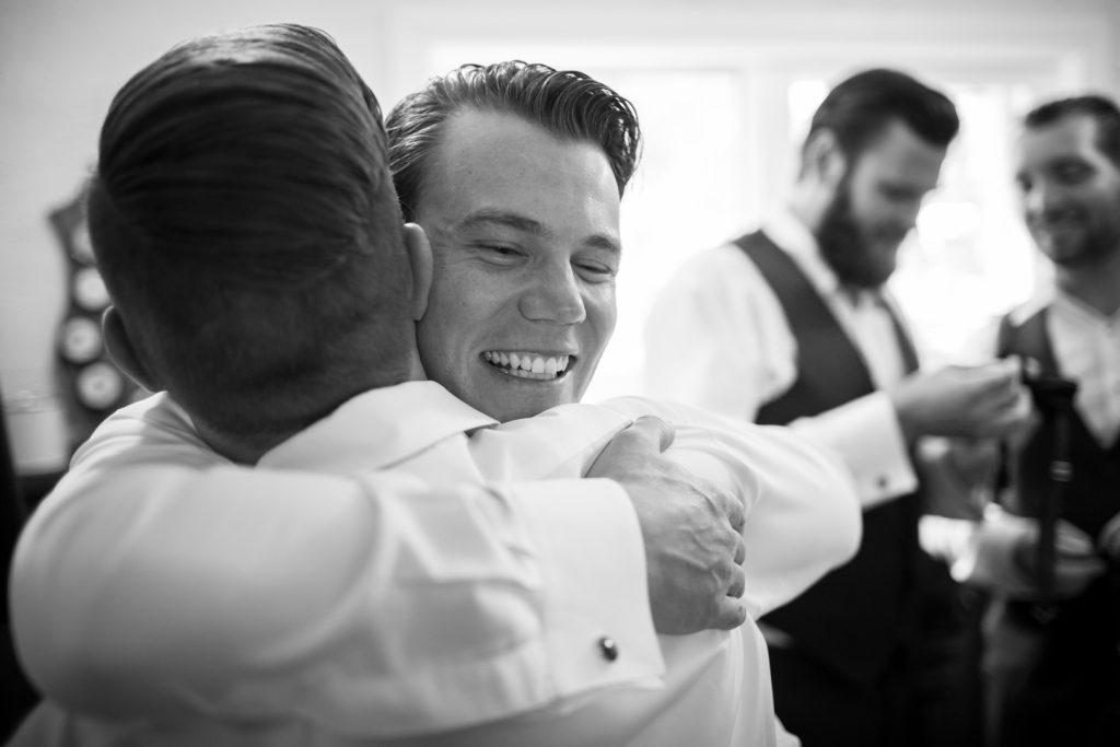 groom hugging his best man as they get ready for the wedding ceremony