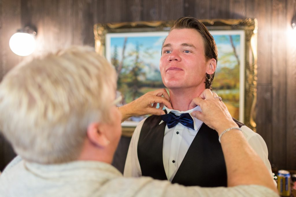 groom getting his bow tie on before the wedding