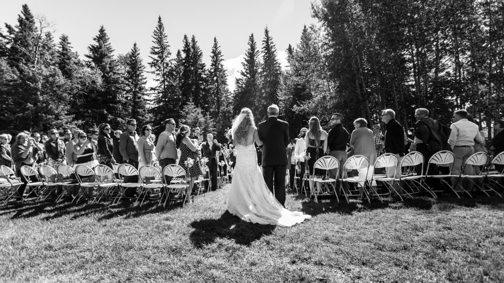 bride being walked down the aisle by her father during outdoor country wedding