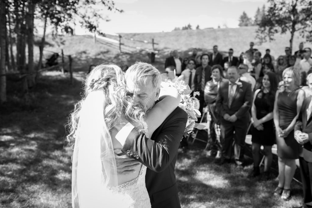 Father of the bride hugs his daughter during the wedding ceremony