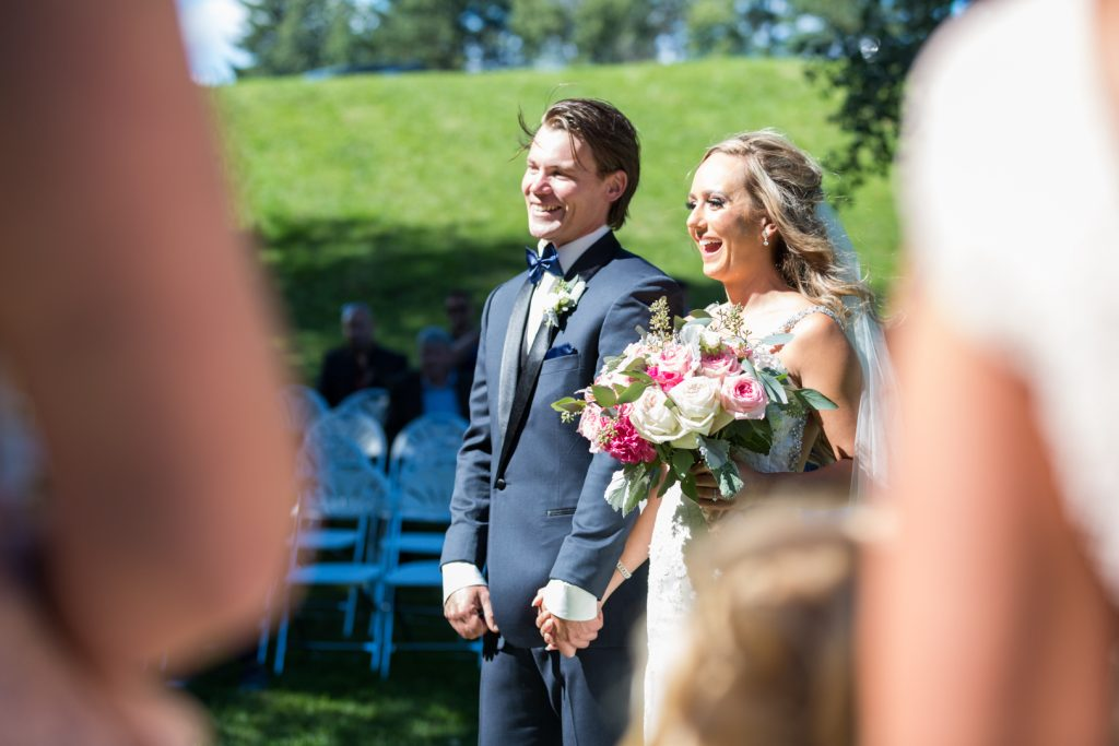 candid photo of the bride and groom laughing during their outdoor country wedding ceremony