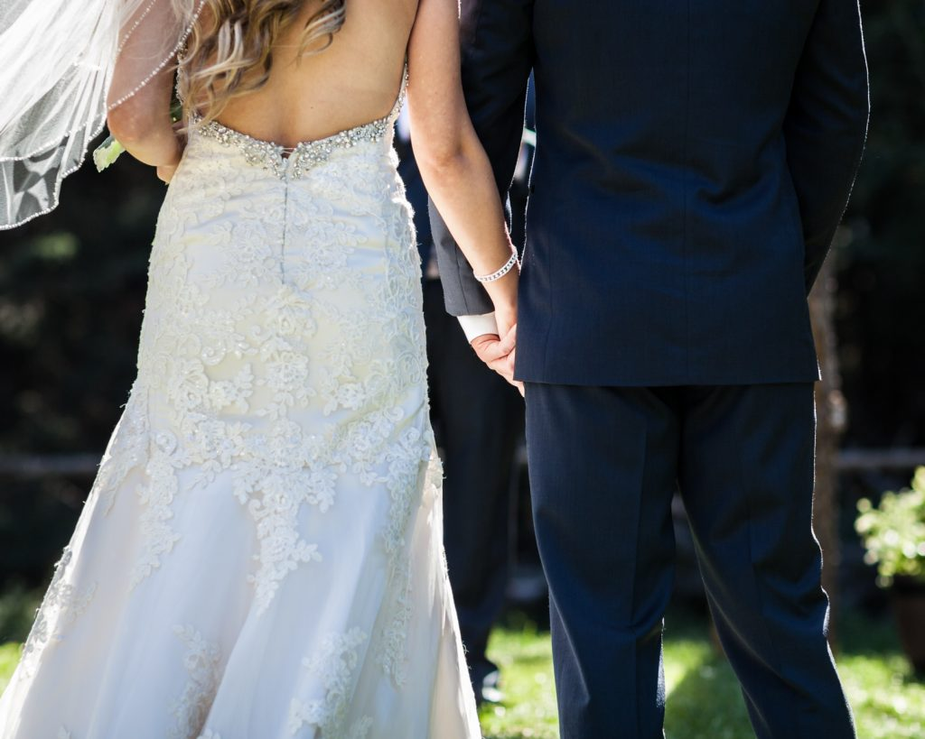 bride and groom holding hands during their outdoor country wedding ceremony