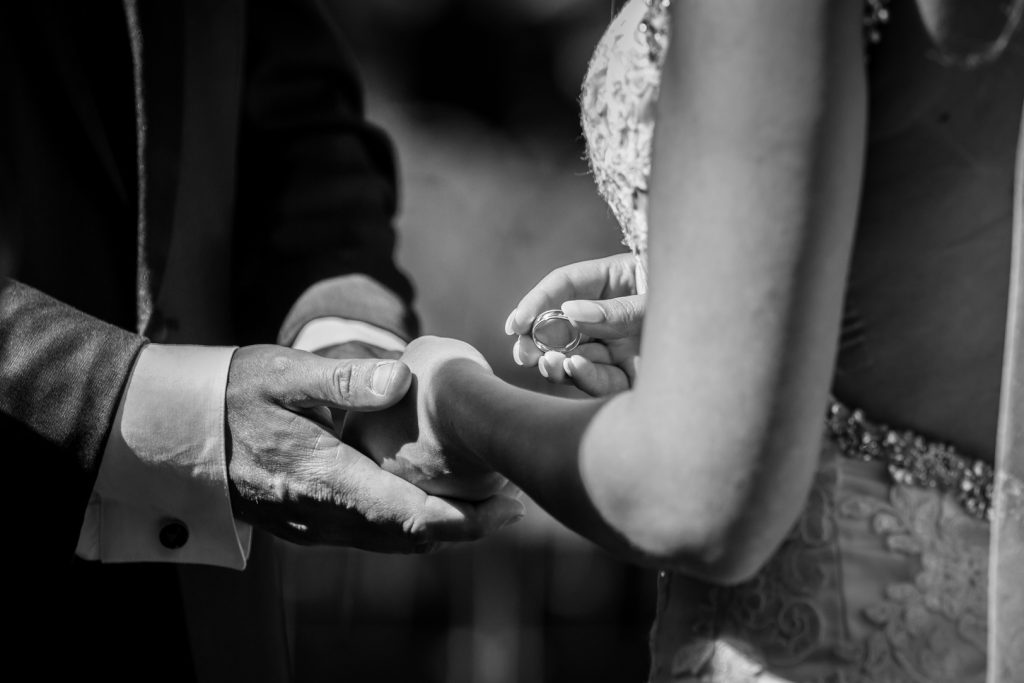 photo of bride putting the ring on her groom