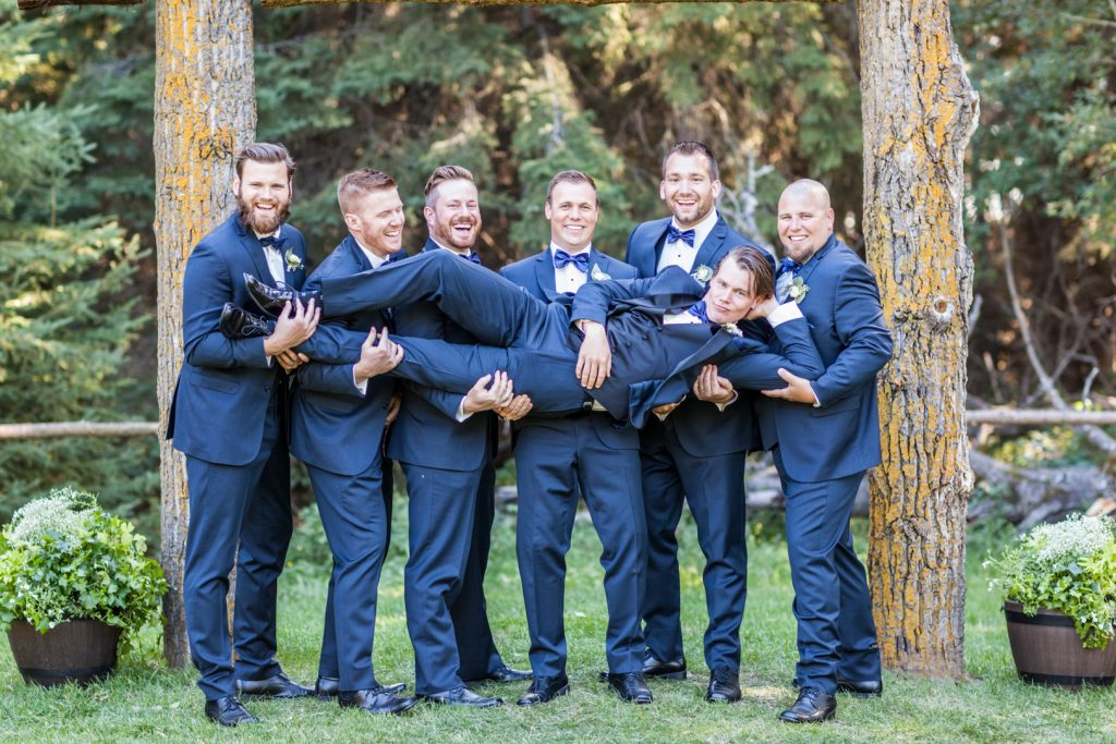 Groomsmen holding the groom for a wedding photo