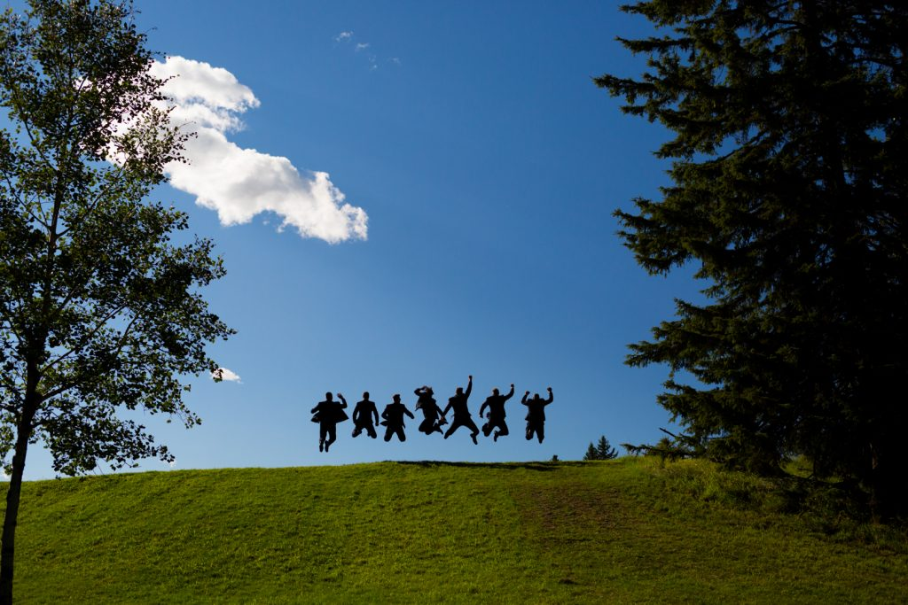 Groomsmen doing an epic jumping photo on top of a hill