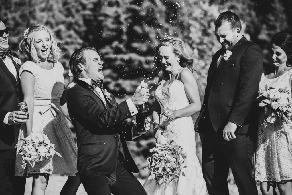 wedding party popping a bottle of champagne