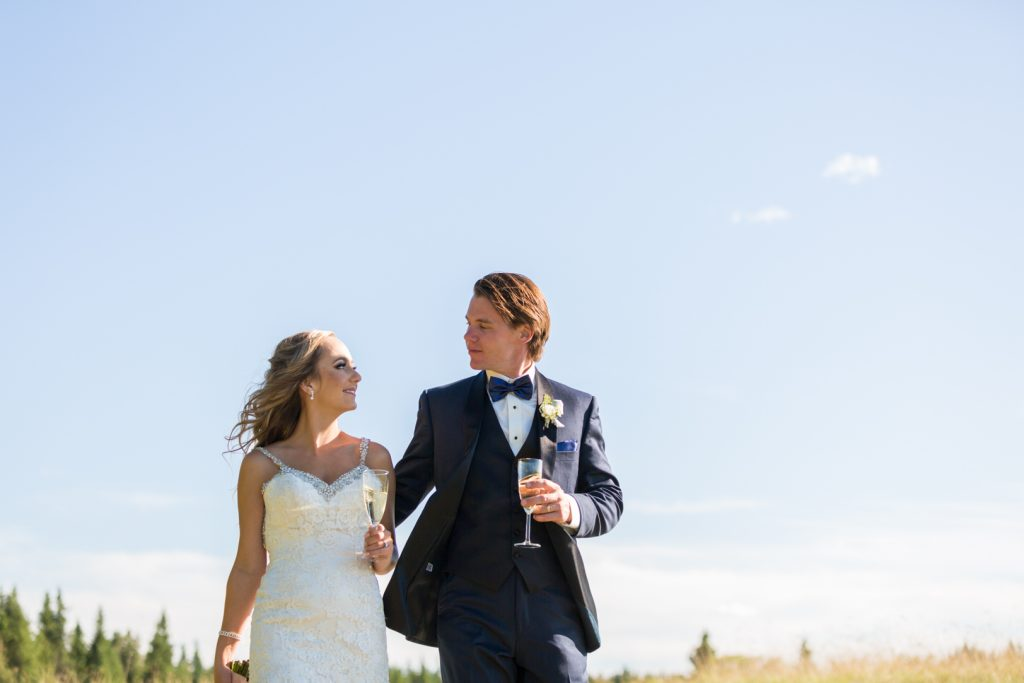 bride and groom walking down the road with glasses of champagne