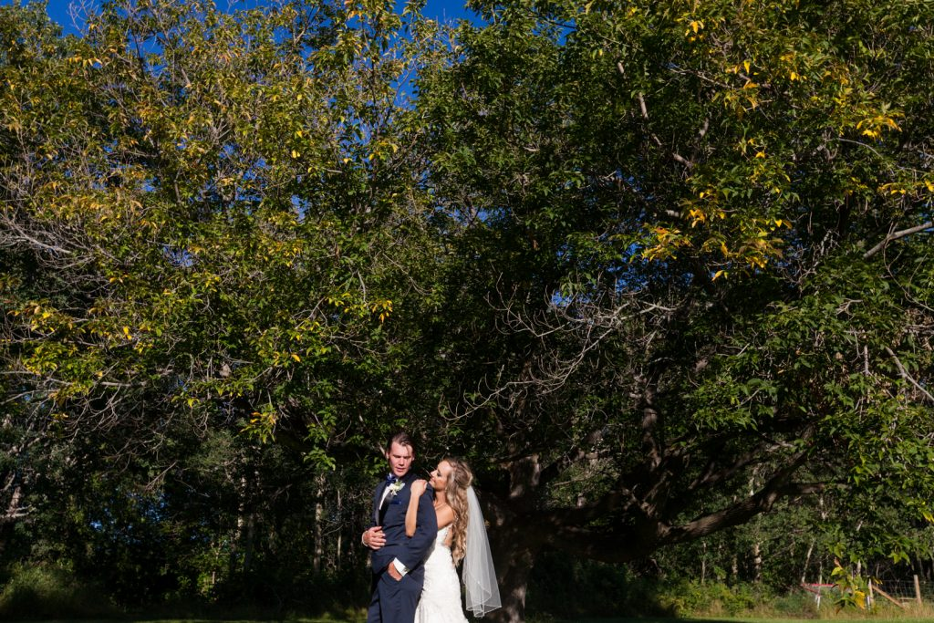 Portrait of bride and groom standing under a large tree