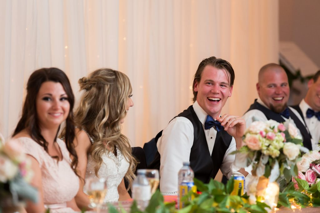 Groom laughing at speeches during wedding reception