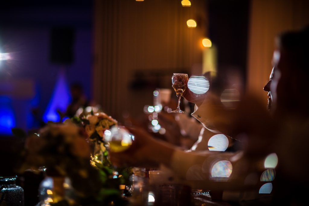 Detail photo of wine glasses during wedding reception speeches