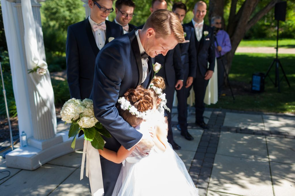 Flower girls giving the groom a hug