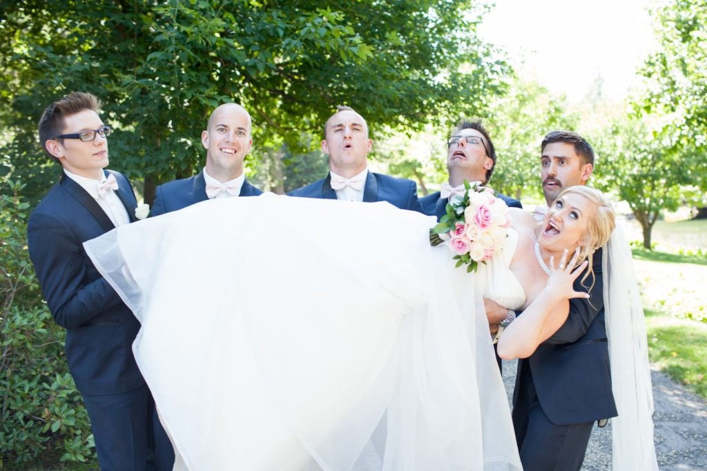 Groomsmen holding up the bride during wedding photos at botanic gardens