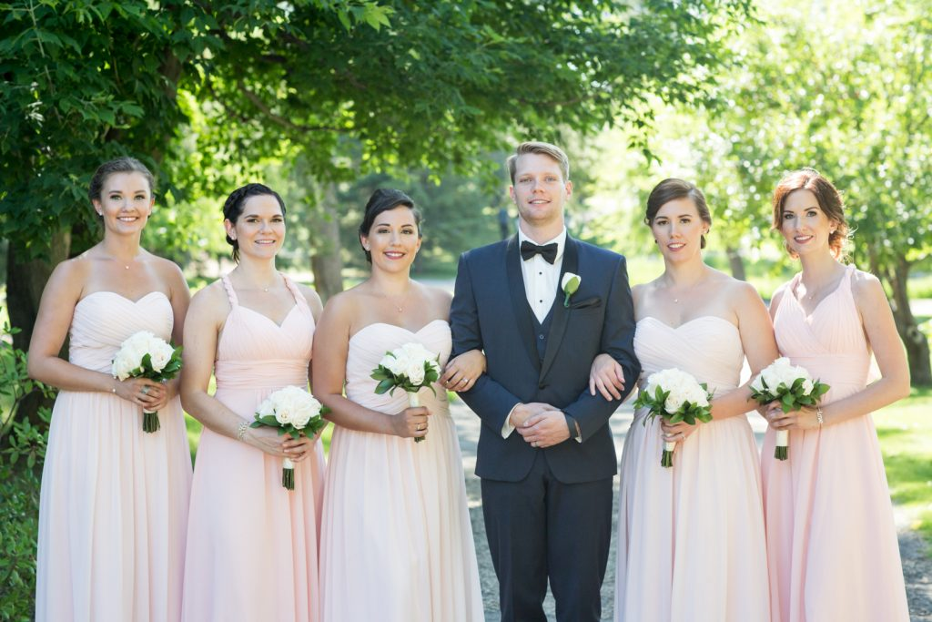 Groom with bridesmaids during outdoor wedding photos in edmonton