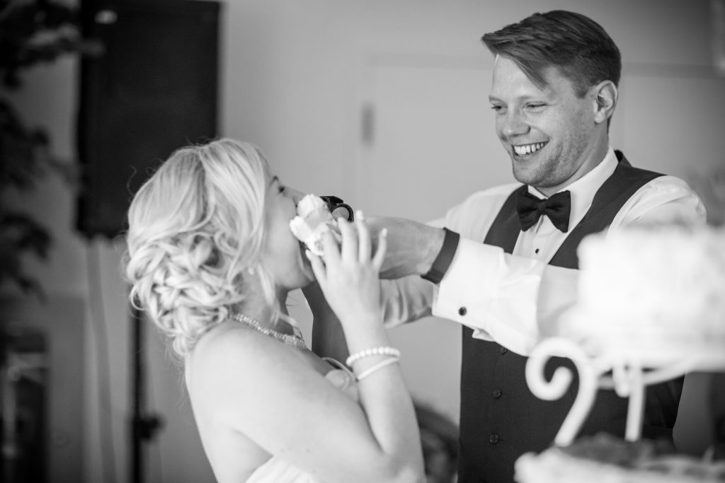 Funny photo of groom feeding the bride wedding cake