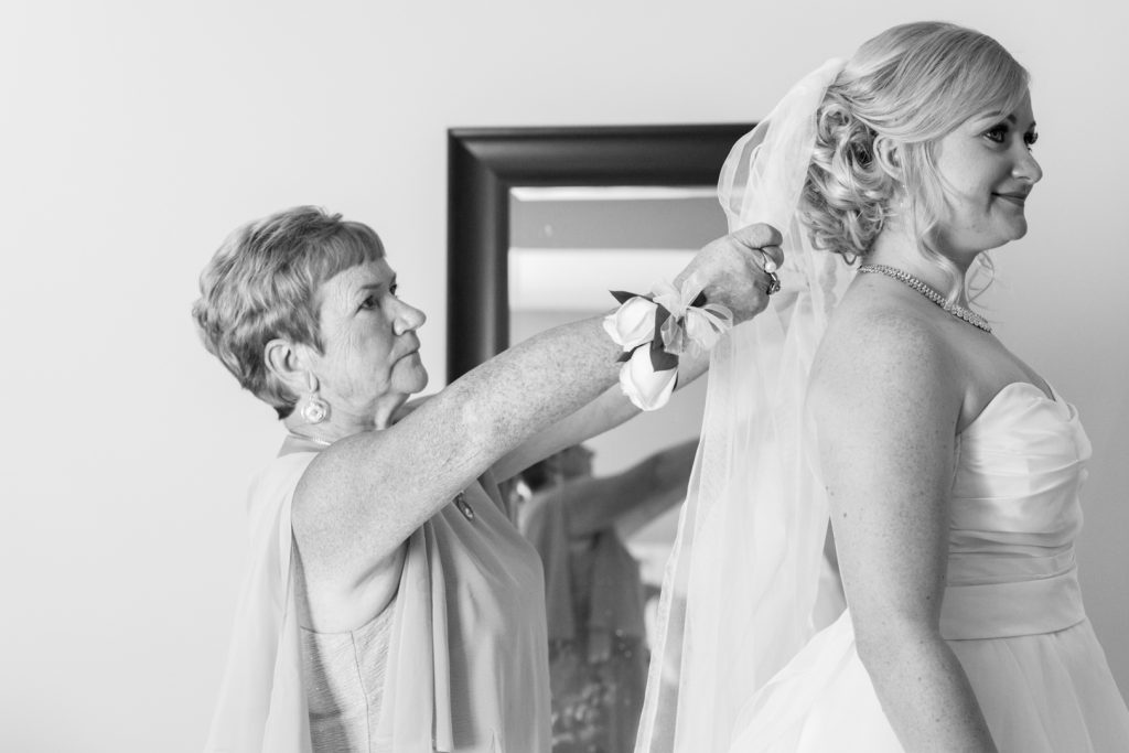 Mother of the bride helping her daughter put in her veil