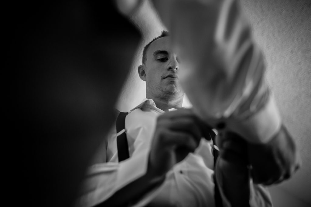 Best man helping the groom with his cufflinks