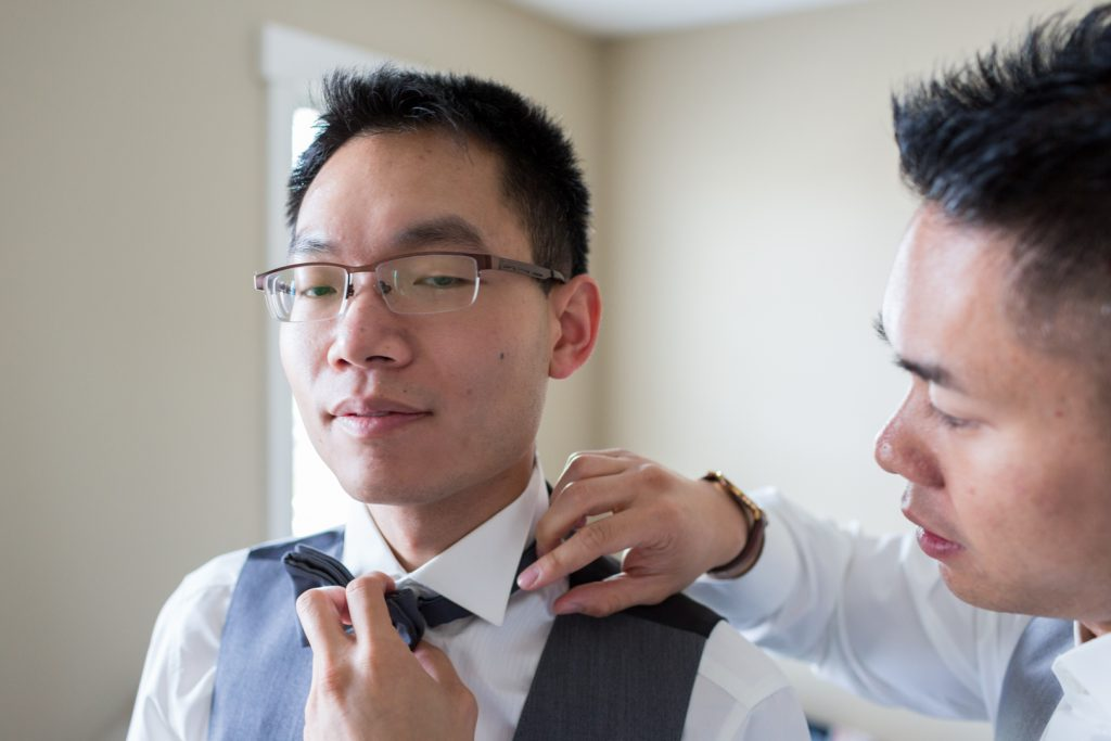 Best man helping the groom with his tie