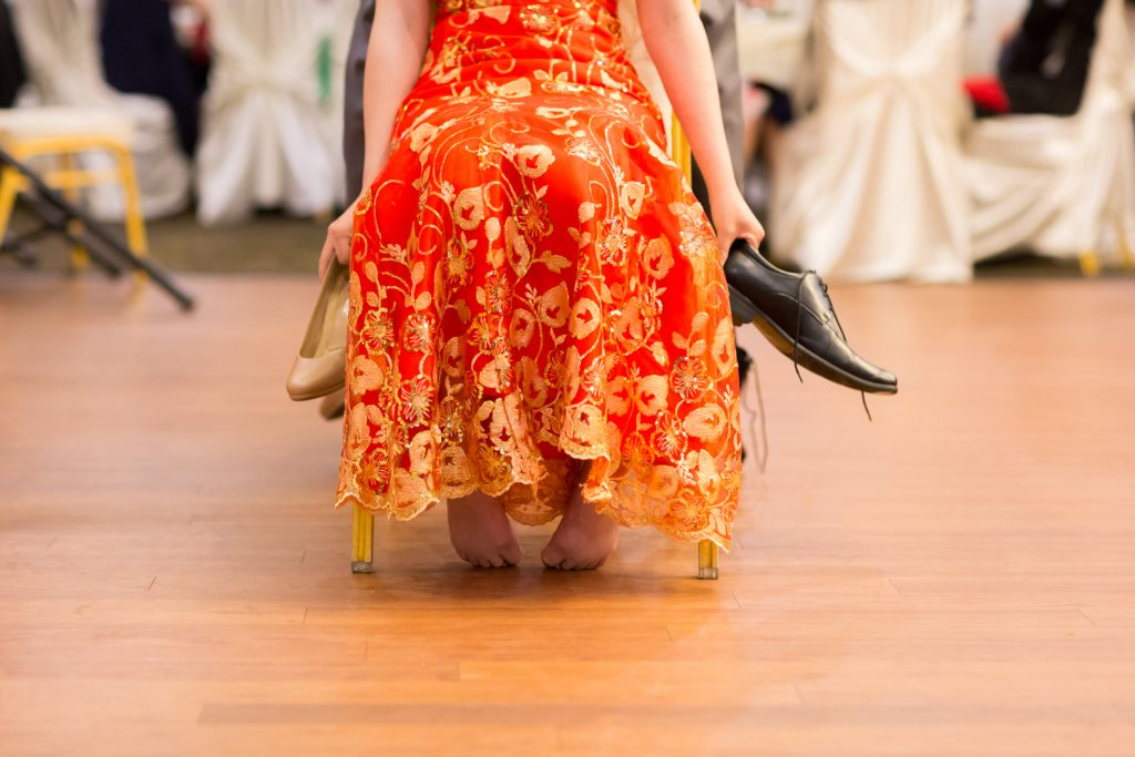 Photo of bride holding onto shoes during the dinner reception shoe game