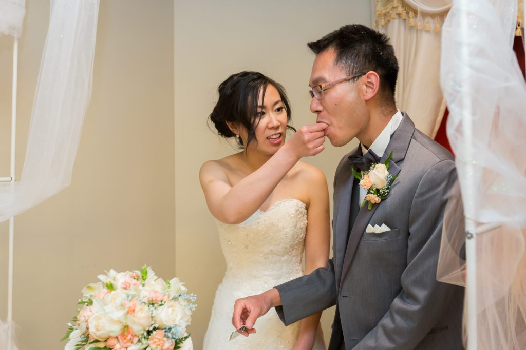 Bride and groom cut the cake and feed each other during their wedding reception